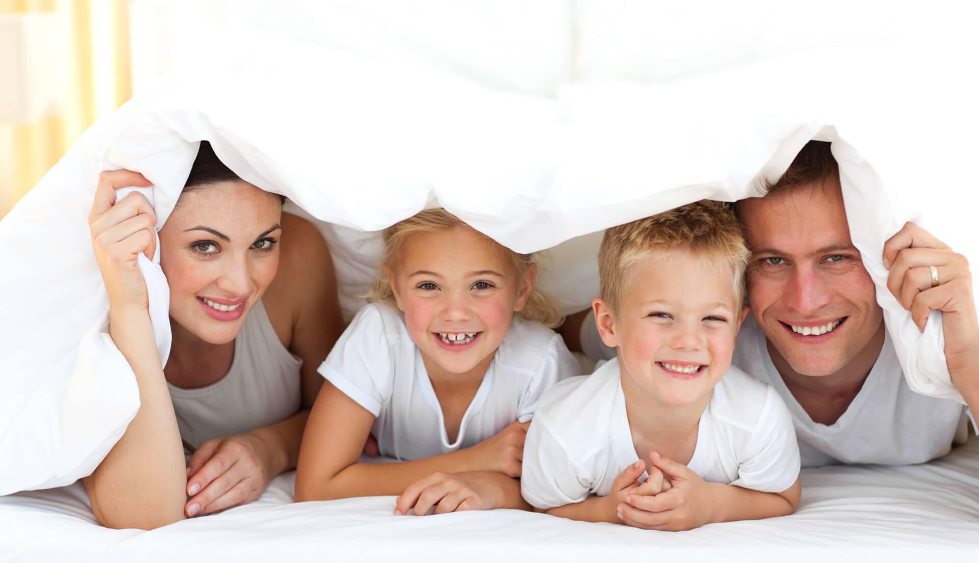 Glückliche Familie unter Zudecke