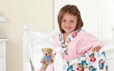 kleines Mädchen im Bademantel mit Teddy